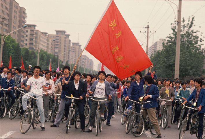 Grupo de estudantes chineses circula de bicicleta em Pequim