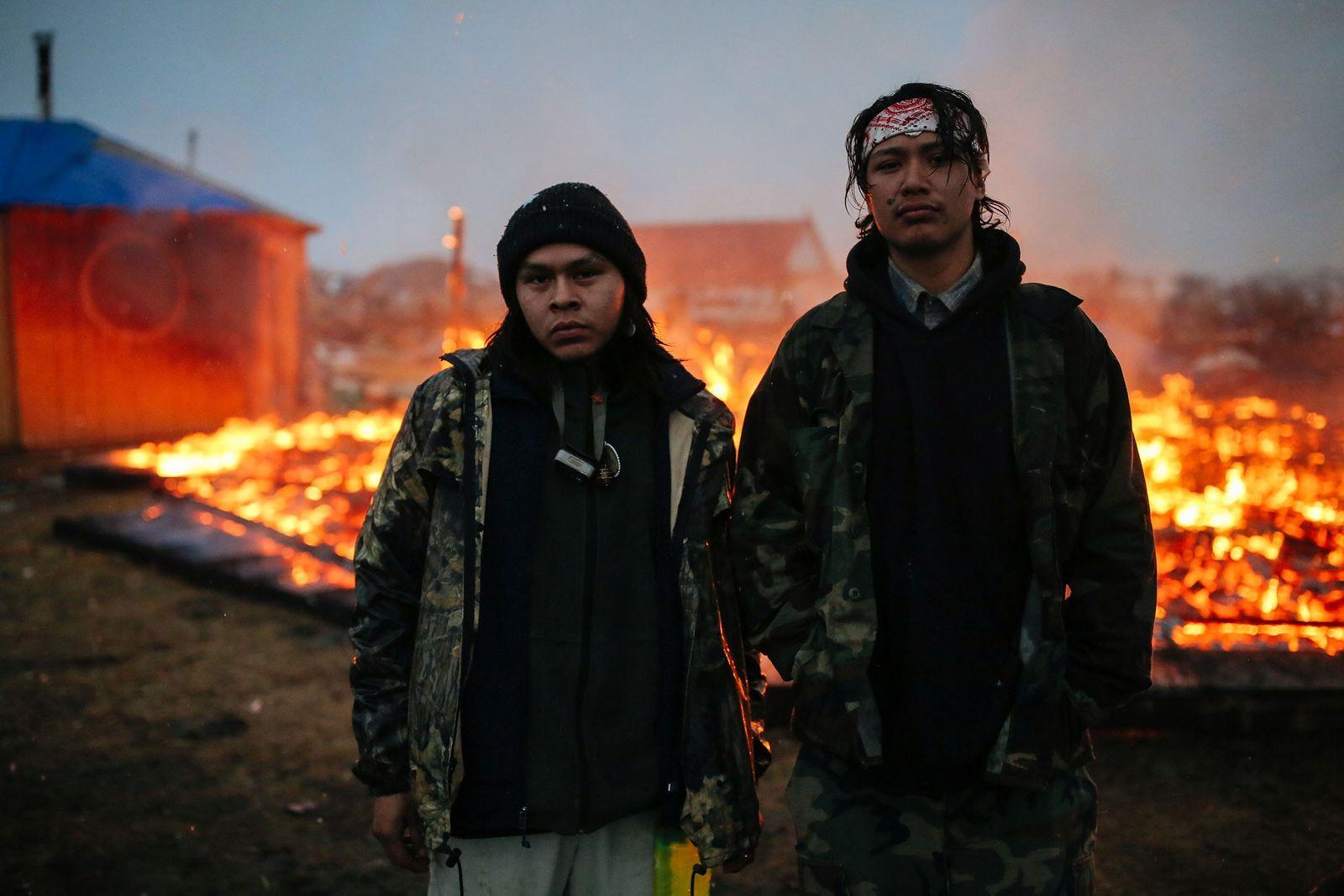 Dois jovens ativistas, que reivindicam o direito à água, são fotografados em frente às ruínas de ...